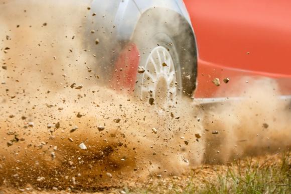 Gravel splashing from stock car drifting on dirt track.