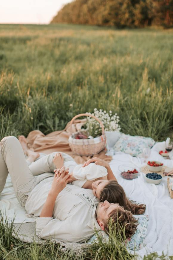 Loving Couple Laying Down After A Picnic In An Open Field